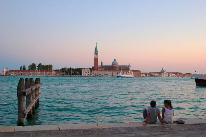 Casal observa as cores do entardecer aos pés da Praça São Marco