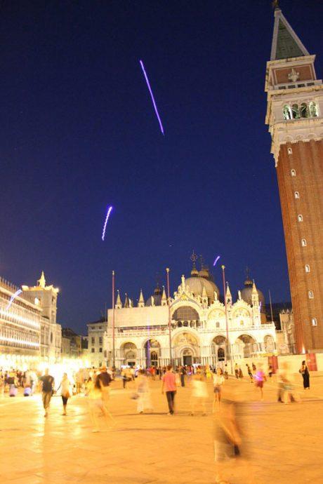 Pequenos brinquedos luminosos recebem os viajantes no céu da Praça São Marco