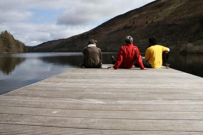 Sentados no píer do lago na Escócia