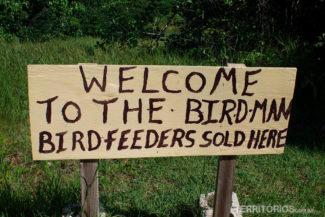 """Placa com mensagem: """"Bem vindo ao Homem pássaro - Vende-se pratos para pássaros"""""""