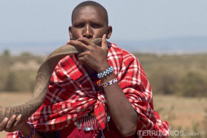 Masai tocando instrumento de chifre protegido com o shuka vermelho (tradicional cobertor)