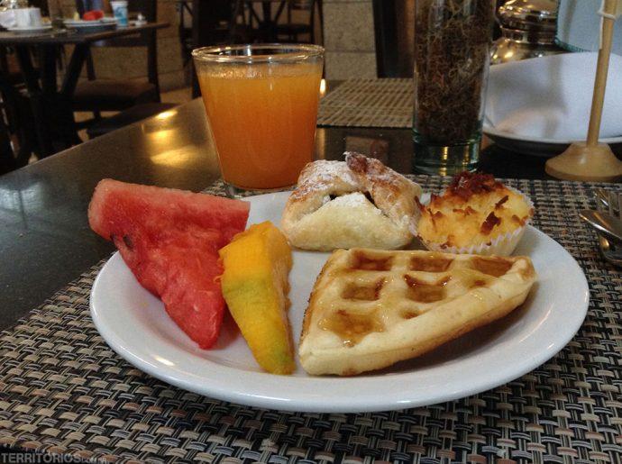 Feliz com frutas e doces no café da manhã