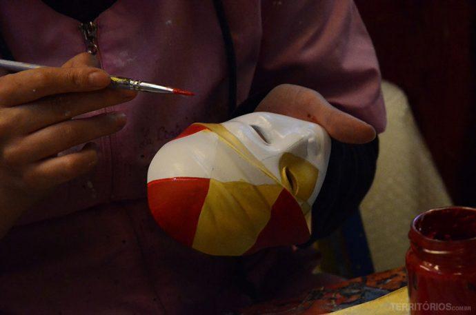 Artista pinta as máscaras dentro da loja