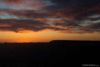 O sol começa a se apresentar atrás do paredão do North Rim