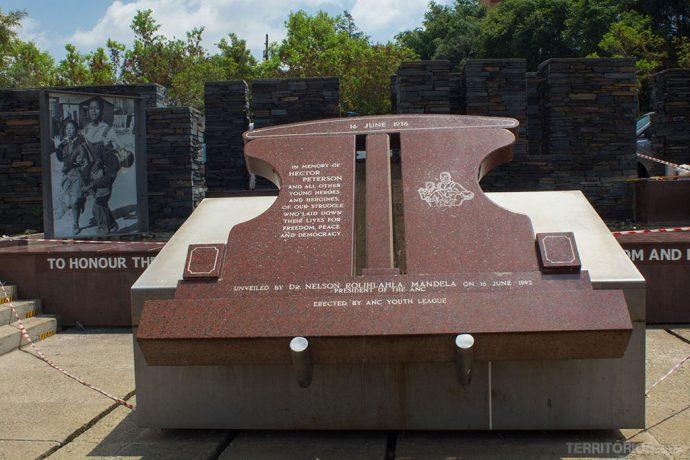 Foto da criança morta ao fundo e monumento em frente ao Museu Hector Pieterson