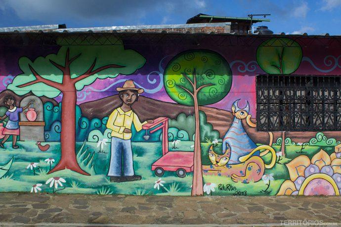 Cotidiano dos moradores de Concepción de Ataco ilustrados nas fachadas das casas