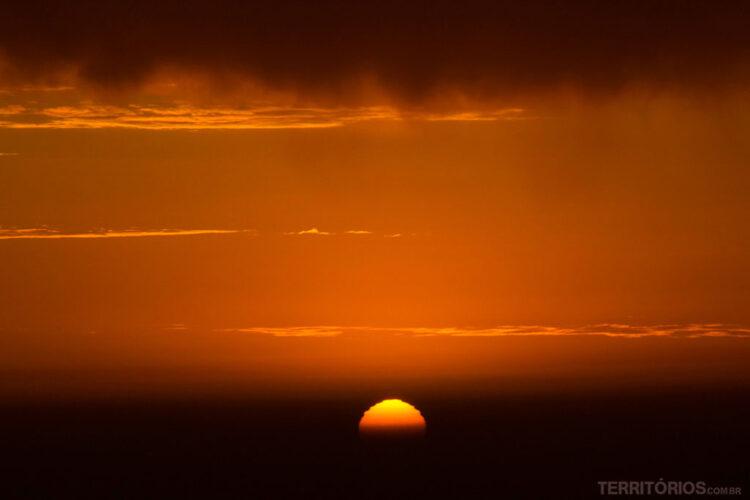 Sol mergulhando na névoa escura sobre o mar