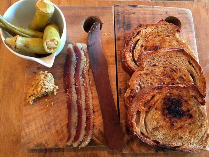 Fatias de pão integral, curado de pato em tiras, mostarda de bergamota e picles de quiabo